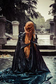 Beautiful vampire woman in palace gate, gothic — Stock Photo