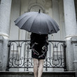 Pretty young woman with black umbrella — Стоковая фотография