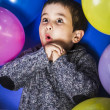 Birthday, child surrounded by balloons at a party — Stock Photo