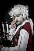 Eighteen era, gentleman rococo wig, candle — Stock Photo