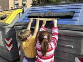 Children pulling a cardboard into recycling container for paper — Stock Photo