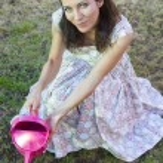 Woman watering green garden — Stock Photo