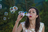 Woman blowing bubbles. — Stock Photo