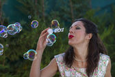 Woman blowing bubbles. — Stockfoto