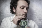 Stingy businessman saving money — Stock Photo