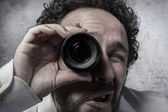 Businessman looking through a lens — Stok fotoğraf