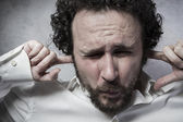 Businessman covering his ears — Stock Photo