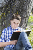 Boy reading a book in the woods — Stock Photo