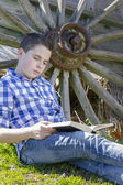 Boy lying beside a wagon wheel — Stock Photo