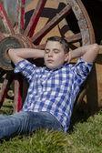Boy lying beside a wagon wheel — Stock Photo