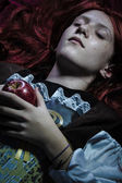 Teen with a red apple lying — Stock Photo