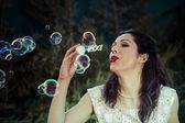 A beautiful woman blowing bubbles — Stock Photo