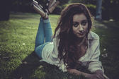 Redhead girl lying on a park — Foto Stock