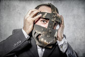 Businessman with iron mask — Stock Photo