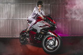Woman in latex mounted on a motorcycle — Stock Photo