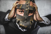 Dangerous business man with iron mask — Stock Photo