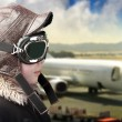 Boy playing with pilot is hat and airport background — Stock Photo #8668650
