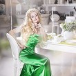 Woman in a green dress posing in the interior — Stock Photo