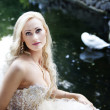 Girl in a white dress on a background of the lake with a swan — Stock Photo
