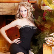 Sexy blonde in a black dress near Christmas tree — Foto de Stock