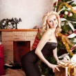 Sexy blonde in a black dress near Christmas tree — Stock fotografie