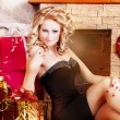 Sexy blonde in a black dress near Christmas tree — Stock Photo