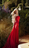 Young beautiful blonde woman in a red dress — Stock Photo