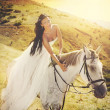 Sensual young beauty riding a horse — Stock Photo