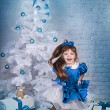Royalty-Free Stock Photo: Cute girl in a blue dress under the Christmas tree