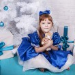 Cute girl in a blue dress under the Christmas tree — Stock Photo