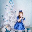 Cute girl in a blue dress under the Christmas tree - Stock Photo