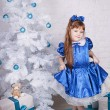 Cute girl in a blue dress under the Christmas tree - Стоковая фотография