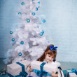 Cute girl in a blue dress under the Christmas tree — Stock Photo #14718729