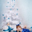 Cute girl in a blue dress under the Christmas tree — Stock Photo #14718731