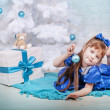 Cute girl in a blue dress under the Christmas tree - Stockfoto