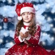 Little girl dressed as Santa Claus under the Christmas tree — Stock Photo #17160939