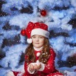 Little girl dressed as Santa Claus under the Christmas tree — Stock Photo #17160995