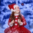 Little girl dressed as Santa Claus under the Christmas tree — Stok fotoğraf