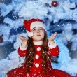 Little girl dressed as Santa Claus under the Christmas tree — Stock Photo #17161075