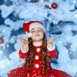 Little girl dressed as Santa Claus under the Christmas tree — Stock Photo #17161083