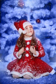 Little girl dressed as Santa Claus under the Christmas tree — Stock Photo