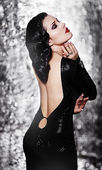 Alluring sexy woman in evening dress posing over dark background — Stock Photo