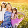 Mother with two daughters in a field of daisies — Stock Photo