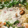 Beautiful teen bride is lying at flowers — Stock Photo