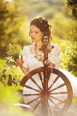 Beautiful bride with old spinning wheel — Stock Photo