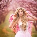Beautiful angel in a flower garden — Stock Photo