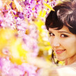 Beautiful girl under blossom acacia tree — Stock Photo #27488923