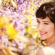 Beautiful girl under blossom acacia tree — Stock Photo