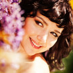 Beautiful girl under blossom acacia tree — Stock Photo #27489043