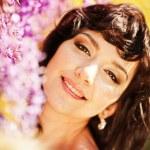 Beautiful girl under blossom acacia tree — Stock Photo